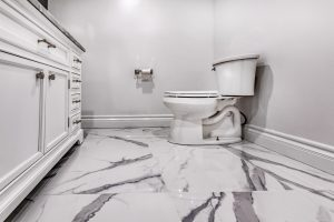 white with grey marble flooring in toilet