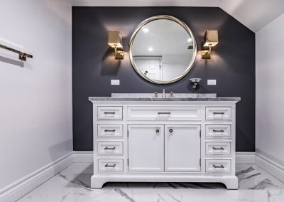 White vanity, charcoal painted wall with wall sconces and round mirror