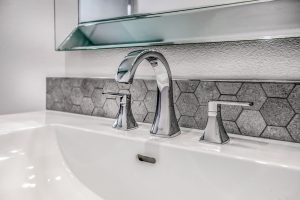 bevelled mirror, chrome faucets and hexagon tile surround