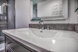 sink vanity and taps with hexagon pattern stone backsplash surround