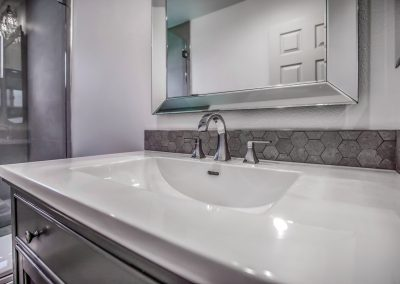 sink vanity and taps with hexagon pattern stone backsplash surround