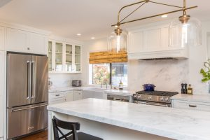 stainless steel fridge and stove with a hood and pendant lights and recessed ceiling lights