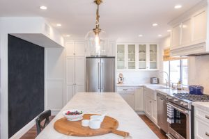 Marble seat at kitchen island with overhead pendant lamps